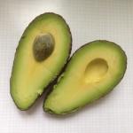 En hel delad avokado i två halvor