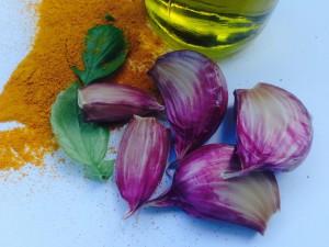 närbild vitlöksklyftor, gurkmejapulver och olivolja på vitt bord