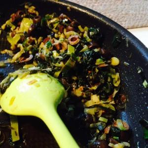 spenat-purjo-oliv-röra i stekpanna med en grön sked