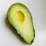 en halv uppskuren avokado på vit bricka