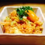 vit skål med avokadorisotto garnerad med gul tomat och färsk oregano