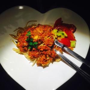 Köttfärssås och spaghetti på vit tallrik med tomat och avokadosallad