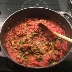 En järngryta med tomat-spenat-sås och en träslev
