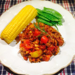 Chili Con Carne serverad på vit tallrik med en majskolv och gröna bönor