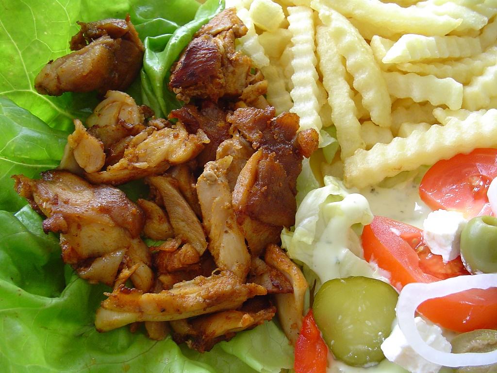 närbild av en portion gyros på kyckling, pommes frites, fetaost, tomat och inlagd gurka på salladsblad