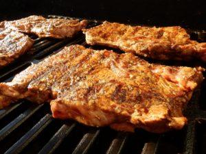 Fyra bitar stekt kött på grillgaller