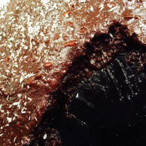 Kladdkaka i stekpanna i närbild varav en skiva är uppskuren så att kladdet syns på kakan