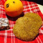 Två pepparkakor med en mandarin och chokladbit på en röd duk