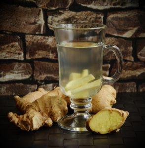 Ett glas med färska ingefärsbitar i vatten samt ingefärsrot på bordet bredvid