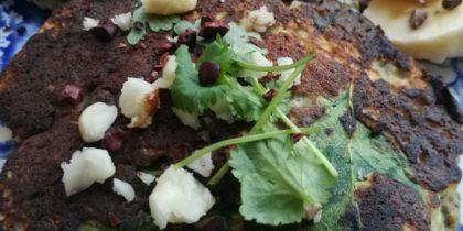 Närbild av två plättar på en tallrik pimpad med nötter och koriander