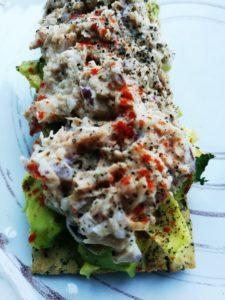 En knäckebit med avokado och tonfiskröra kryddad med paprika och svartpeppar tagen i närbild på en vit tallrik