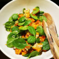 Vit skål med salladen med två träbestick i