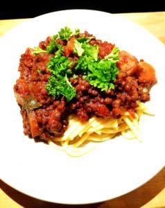 En tallrik med bolognese och spaghetti dekorerad med persilja