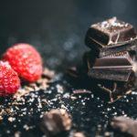Några rutor mörk choklad och två hallon i närbild