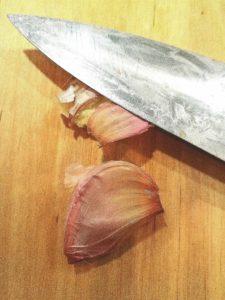 två vitlöksklyftor på en skärbräda varav ena krossas med ett knivblad