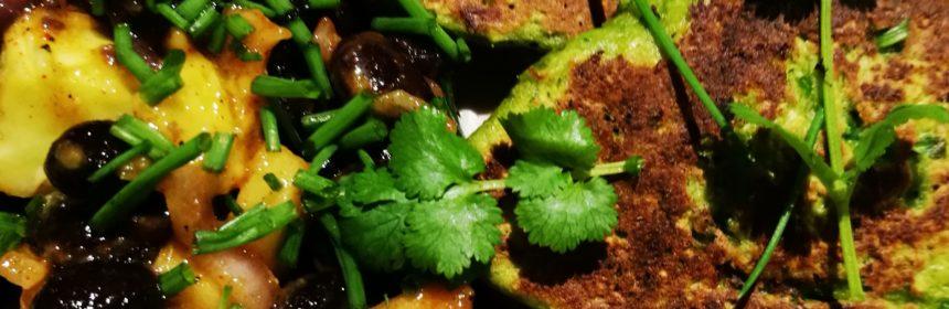 Två majsfritters med bönsalsa toppad med färsk koriander på en vit tallrik i närbild
